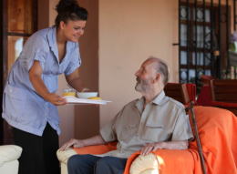 caregiver giving food to senior man