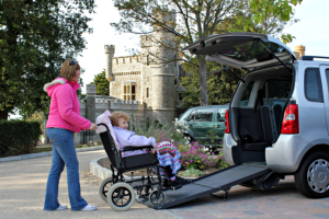 assisting senior woman getting inside the car
