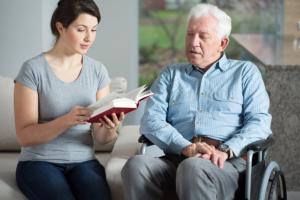 nursing assistant assisting senior man in reading